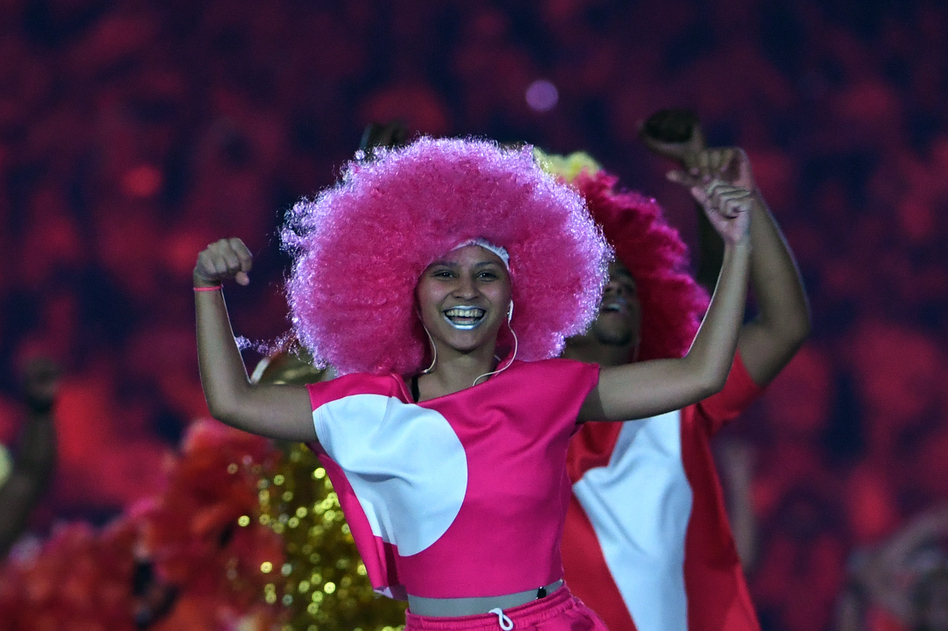 The music pumps and the colors explode on the stage as dancers move. (AFP/Getty Images)