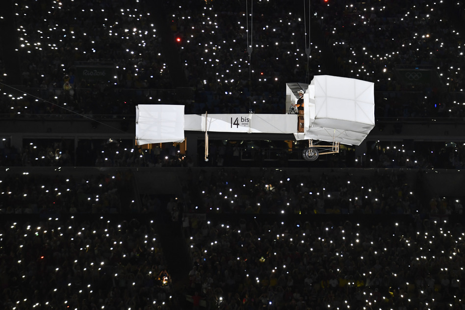 A wright-brothers style aircraft forms part of the opening ceremony flown by a gentleman in old-fashioned clothes.  (Getty Images)