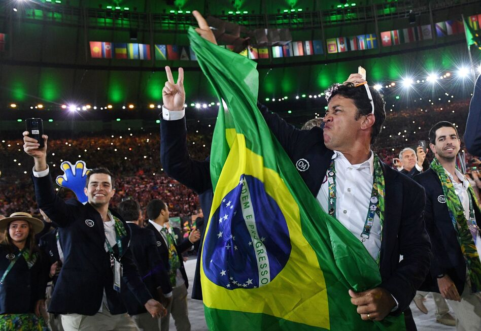 """A member of the Brazil delegation waves a flag. The athletes and staff are dancing as a long remix of the classic 1939 song """"Aquarela do Brasil"""" — known to many English-speakers simply as """"Brazil"""" — plays. (AFP/Getty Images)"""