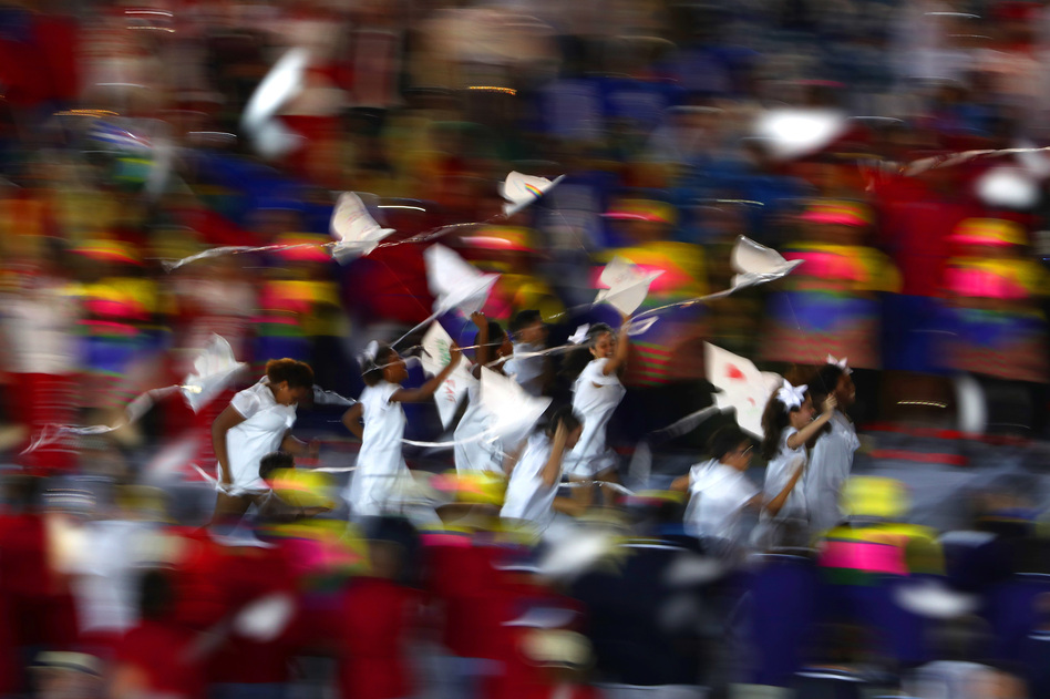 A group of children run onto the stage carrying small dove kites with Kipchoge Keino, 72 — a former Olympian who won two gold medals and is now the chairman of the Kenyan Olympic Committee. Keino is the first-ever winner of the Olympic Laurel award. (Getty Images)