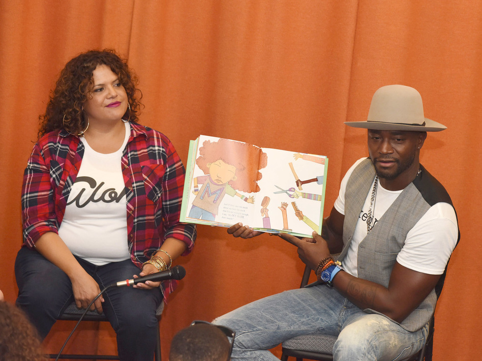 Fashion designer Sonia Smith-Kang sits with actor Taye Diggs as he reads his book, Mixed Me, to children in Los Angeles in 2015. (Getty Images for Mixed Up Clothing Inc.)
