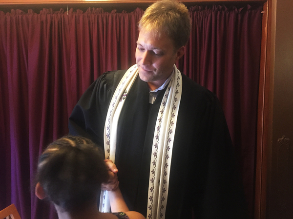 The Rev. Seth Kaper-Dale shakes hands after a service at the Reformed Church of Highland Park.