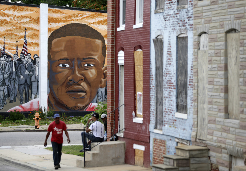People walk by a mural depicting Freddie Gray in Baltimore on June 23, at the intersection where Gray was arrested in 2015. (Patrick Semansky/AP)