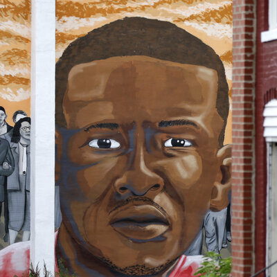 People walk by a mural depicting Freddie Gray in Baltimore on June 23, at the intersection where Gray was arrested in 2015.