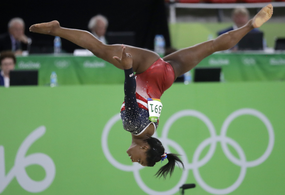 Simone Biles of the U.S. performs on the floor during the women's team final on Tuesday. Biles led the American squad to a runaway victory as the U.S. successfully defended the gold they won four years ago. (Julio Cortez/AP)