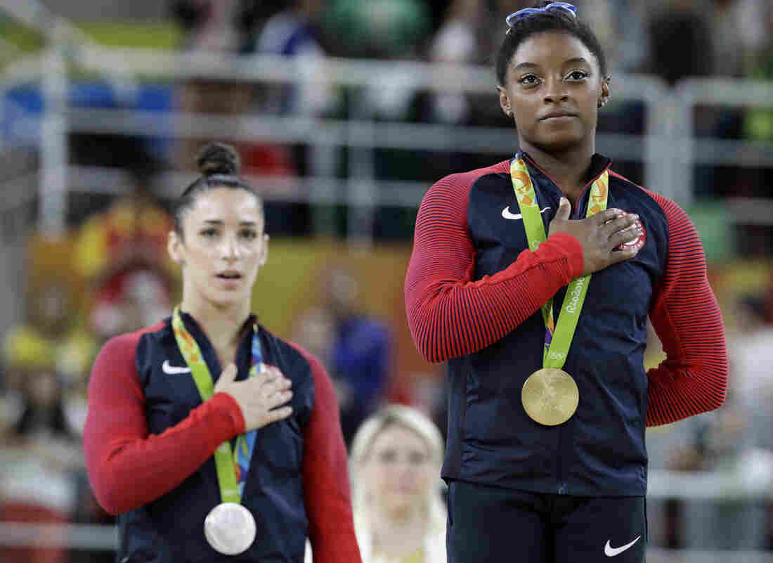 Gold medalist Simone Biles (right) and silver medalist Aly Raisman sing the U.S. national anthem during the medal ceremony for the women's individual all-around on Thursday.