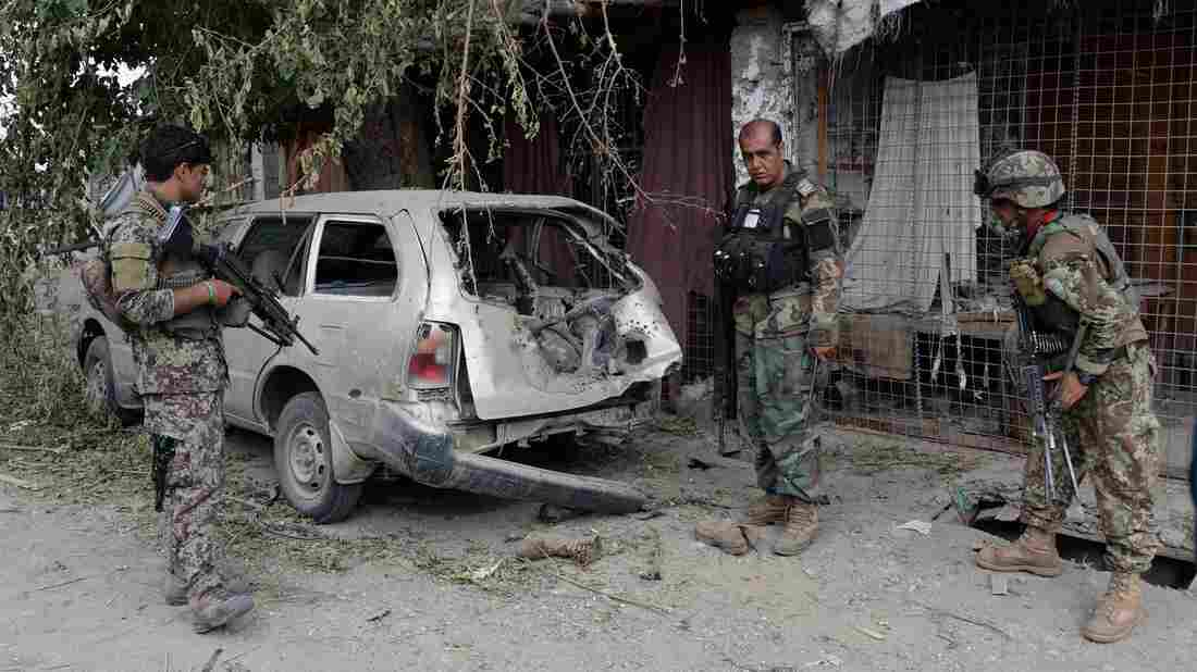 Afghan soldiers inspect a destroyed vehicle after an operation in Nangarhar province, Afghanistan, on July 26, the day the Pentagon says a drone strike killed the leader of the Islamic State in the region.
