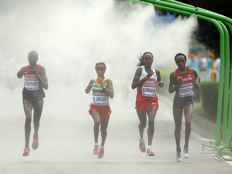Helah Kiprop of Kenya, Eunice Jepkirui Kirwa of Bahrain and Mare Dibaba of Ethiopia enter a cooling station during the Women's Marathon final during day nine of the 15th IAAF World Athletics Championships Beijing 2015 at Beijing National Stadium on August 30, 2015 in Beijing, China.