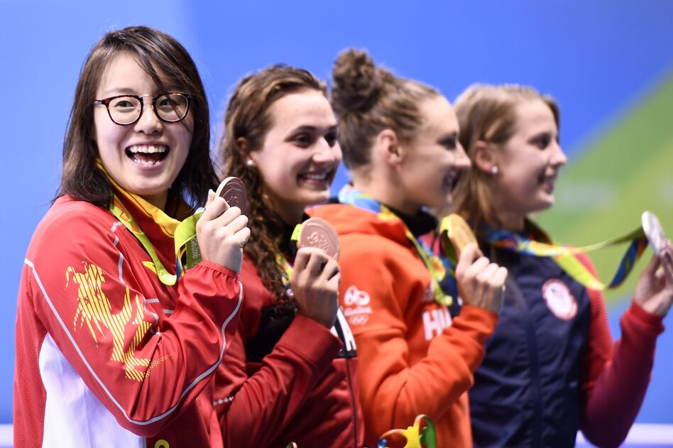 China's Fu Yuanhui (left) celebrates her bronze medal win in the women's 100-meter backstroke with Canada's Kylie Masse, Hungary's Katinka Hosszu and the U.S.'s Kathleen Baker. (Christophe Simon/AFP/Getty Images)