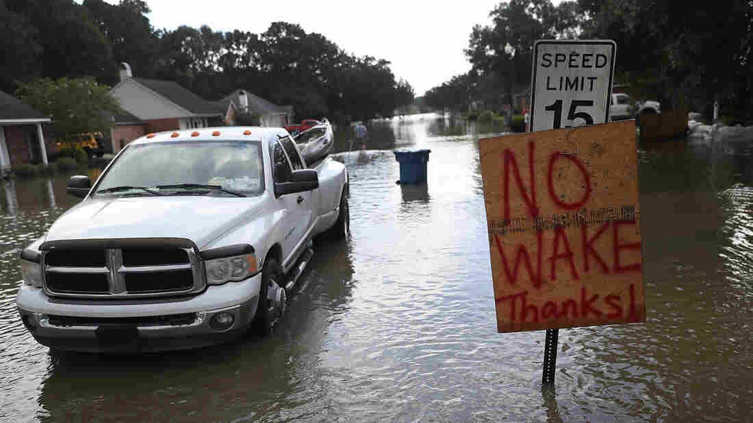 "A ""no wake"" sign is seen along side a street in a residential neighborhood inundated with floodwaters this week in Sorrento, La."