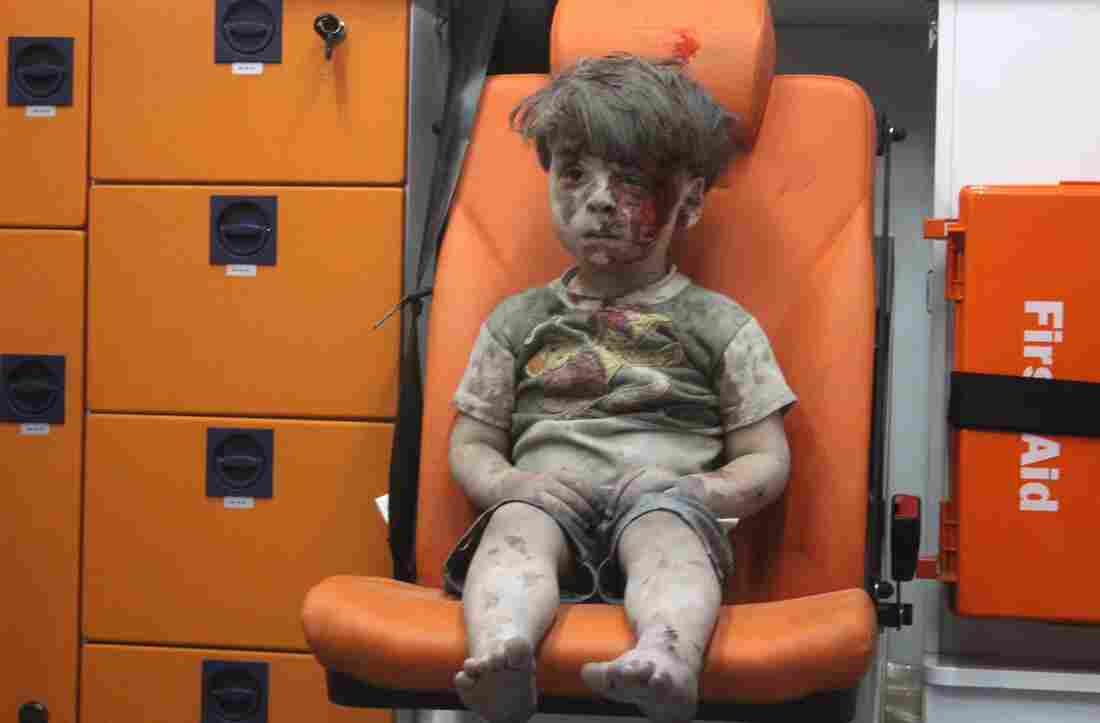 A 5-year-old boy, identified in news reports as Omran Daqneesh, sits in an ambulance Wednesday after reportedly being pulled out of a building hit by an airstrike in Aleppo, Syria.
