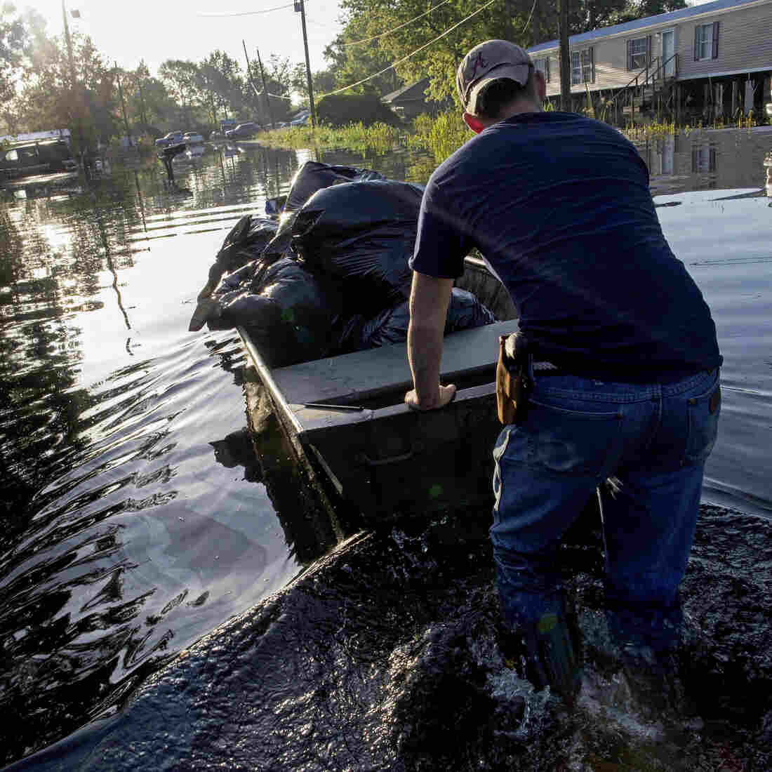 Daniel Stover, 17, moves a boat of personal belongings from a friend's flooded home in Sorrento, La., on Saturday.