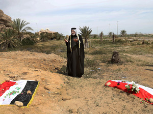 An Iraqi man prays in 2015 for his slain relative, at the site of a mass grave, believed to contain the bodies of Iraqi soldiers killed by Islamic State group militants when they overran Camp Speicher military base, in Tikrit, Iraq.
