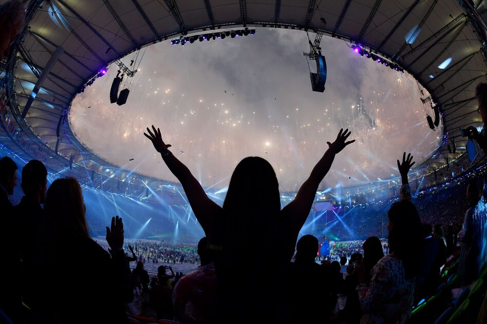 Spectators dance as fireworks light up the sky during the closing ceremony of the Rio 2016 Olympic Games on Sunday. (Fabrice Coffrini/AFP/Getty Images)