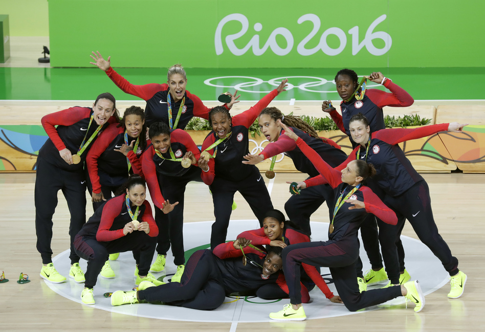 The U.S. women's basketball team poses Saturday after winning its sixth straight gold medal and its 49th straight game in the Olympics. The team's success reflects the growing dominance of U.S. women in recent Olympiads. The U.S. women have won more medals than the American men in the past two Summer Games. (Charlie Neibergall/AP)