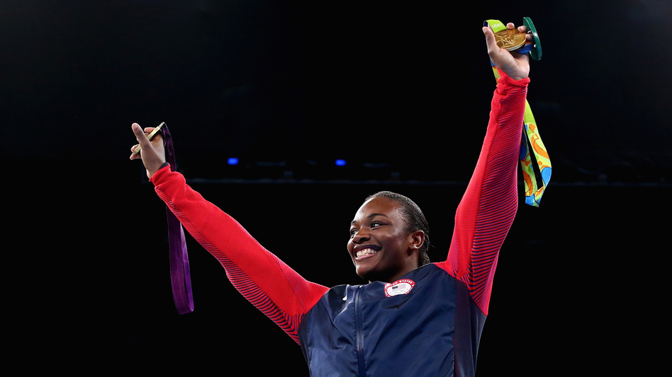Boxer Claressa Shields holds her gold medals from the 2012 and 2016 Olympic Games during the medal ceremony on Sunday. She is the first U.S. boxer to win consecutive Olympic gold medals. (Getty Images)