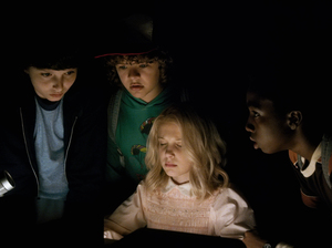 A mysterious young girl (Millie Bobby Brown) helps three boys (Finn Wolfhard, Gaten Matarazzo, Caleb McLaughlin) look for their missing friend in Netflix's Stranger Things.