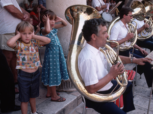Children cover their ears while listening to a brass band perform.