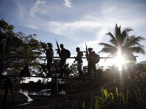 Rebels of the 48th Front of the Revolutionary Armed Forces of Colombia walk on a makeshift footbridge in the southern jungles of Putumayo on Aug. 12. On Wednesday, it was announced that the FARC and the Colombian government had reached a deal to end their decades-long conflict.
