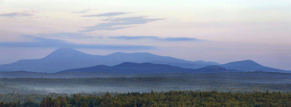 Early morning haze colors Mount Katahdin and its surrounding mountains as seen in 2014 from a height of land along Route 11 in Patten, Maine. The viewpoint is part of the Katahdin Woods & Waters scenic byway. (Gregory Rec/Portland Press Herald via Getty Images)