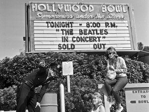 Officer Robert Yocum informs Beatle fans Chelie Mylott and Melody Yapscott, right, that they'll have to move from their spot in front of the Hollywood Bowl. The women had no tickets but hoped to get them from scalpers or sneak in. This photo was published in the Aug. 24, 1964 Los Angeles Times.