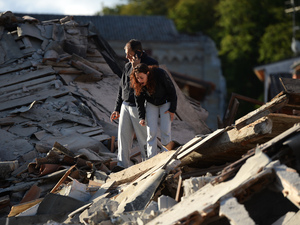 Residents stand among damaged buildings after a strong earthquake hit Amatrice on Wednesday. Central Italy was struck by a powerful, magnitude 6.2 earthquake in the early morning.