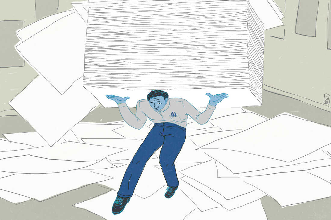 Man carrying huge stack of papers, with papers strewn about