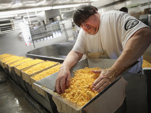 Lenny Zimmel puts Colby cheese curds into forms to make 40 pounds blocks of cheese at the Widmer's Cheese Cellars in Theresa, Wis. Record dairy production in the U.S. has produced a record surplus of cheese, causing prices to drop.