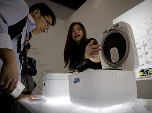 An exhibitor shows a smart rice cooker to a visitor at a display booth for MiJia, a new brand by Xiaomi at the 2016 Global Mobile Internet Conference in Beijing on April 28.