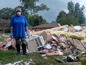 Myra Engrum stands by the huge pile of her and her son's belongings, plus all the wet building materials that have been pulled out of her flooded house.