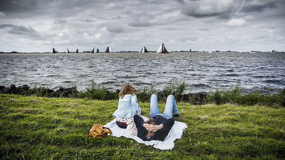 People at leisure watch boats taking part in the sixth race of the Skutsjesilen competition, a traditional boat race of sailing yachts from several Frisian cities, in Elahuizen, on August 5. (AFP/Getty Images)