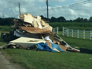 Debris from flood-damaged homes lines Highway 167 in Maurice, La.