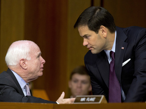 Sen. John McCain, R-Ariz., and Sen. Marco Rubio, R-Fla., talk on Capitol Hill in 2014. Both are expected to win their primaries for reelection Tuesday.