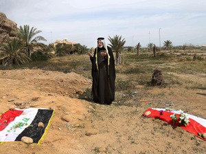 An Iraqi man prays for his slain relative at the site of a mass grave, believed to contain the bodies of Iraqi soldiers killed by Islamic State group militants when they overran Camp Speicher military base, in Tikrit, Iraq, in April 2015.