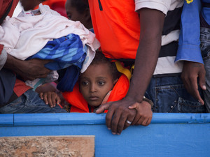 A boy looks on inside a crowded wooden boat carrying more than 700 migrants before being rescued, about 13 miles north of Sabratha, Libya. The boat was one of 40 vessels rescued on Monday.