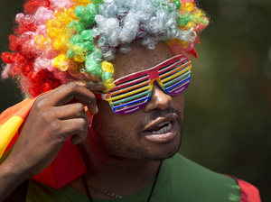 A protester in a rainbow-colored wig and glasses joins a 2014 rally in Kenyan to protest Uganda's increasingly tough stance on homosexuality.