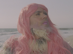 "A pink yeti struts the beach in a scene from Deap Vally's video for the song ""Gonnawanna."""