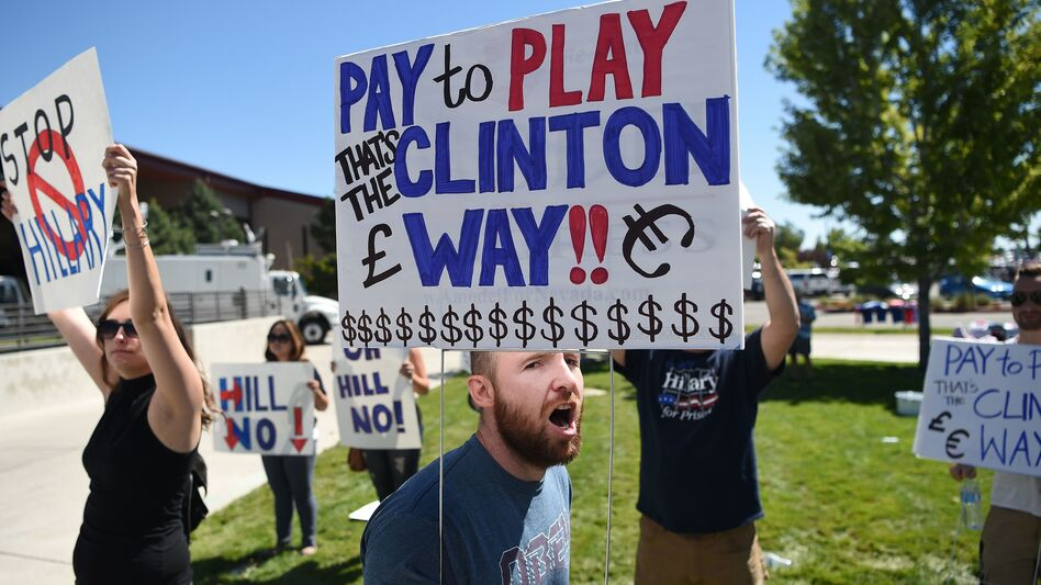 Protesters shout as people wait to enter a Hillary Clinton campaign event last month in Nevada. Donald Trump is calling for a special prosecutor to investigate allegations of pay-to-play by Clinton, but the history of independent counsels and special prosecutors suggests they don't always remove politics from the process. (Josh Edelson/AFP/Getty Images)