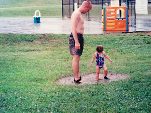 Chris and 1 1/2-year-old Kayley play in mud puddles.