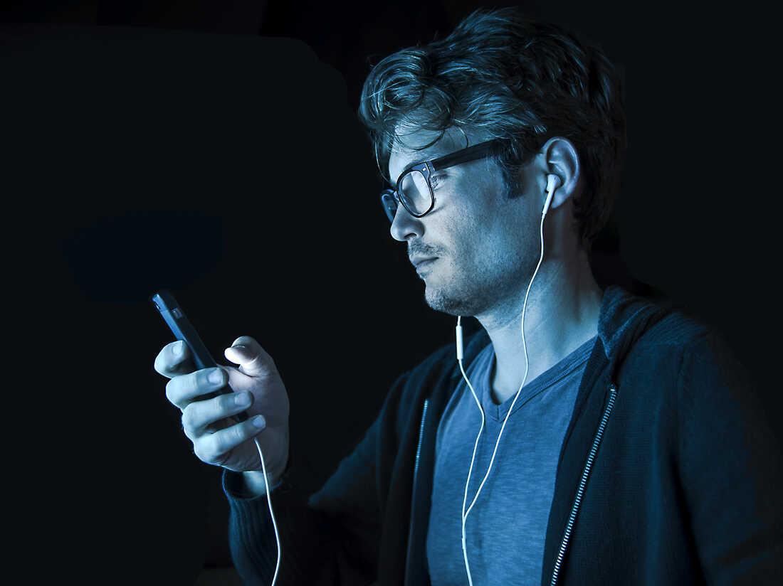 A man listens to an iPhone.
