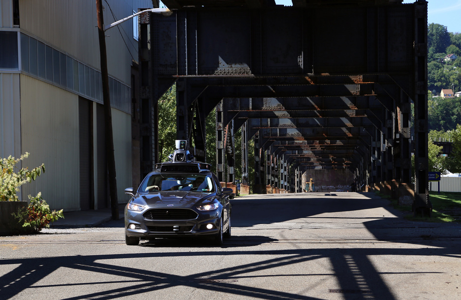 A self-driving car leaves Uber's newest riverside hub in Pittsburgh. Company officials say the Rust Belt city is perfect for beta testing, citing diverse topography, frequent weather maladies, near-constant construction and hundreds of bridges and tunnels. (Megan Harris/WESA)