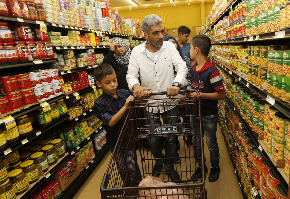 Nadim Fawzi Jouriyeh, a Syrian refugee who arrived in the United States in August with his family, pushes a shopping cart in El Cajon, Calif. (Lenny Ignelzi/AP)