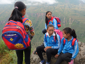 Ethnic Yi schoolgirls take a break halfway down the mountain, on their way from their homes in Atule'er village to their first day of school in a new semester. The difficulty of getting up and down the mountain has made it hard for villagers to shake off poverty, and made it challenging for their children to attend school.