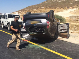 An Israeli security officer next to an overturned vehicle belonging to a family of Jewish settlers ambushed near Hebron, in the West Bank, on July 1. Two Palestinians aided the wounded Israelis. One of the Palestinians has since lost his job and been targeted for abuse by fellow Palestinians.