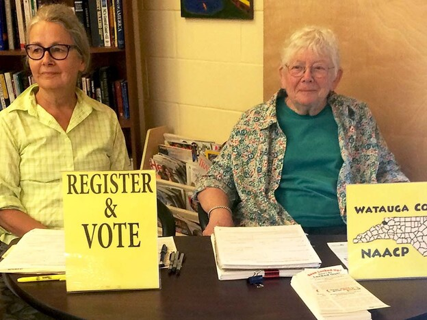 NAACP volunteers Marjorie McKinney (left) and Joan Brannon sit at a booth to register people to vote at the Hospitality House, a community shelter in Boone, N.C.