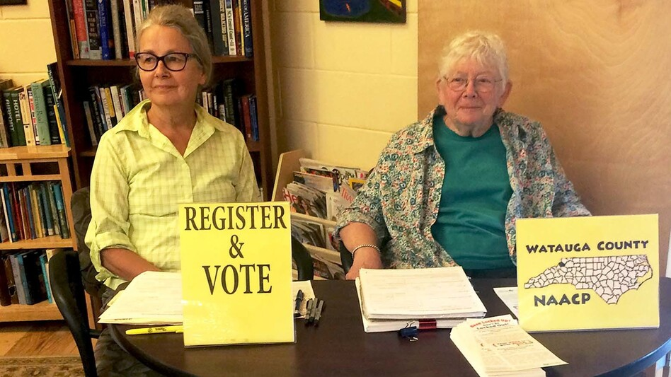 NAACP volunteers Marjorie McKinney (left) and Joan Brannon sit at a booth to register people to vote at the Hospitality House, a community shelter in Boone, N.C. (NPR)