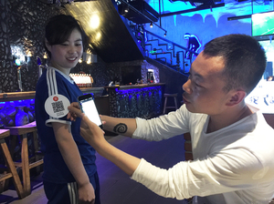 Beijing-based restaurateur Song Ji (right) demonstrates his system, which allows customers to tip wait staff. Diners use smartphones to scan QR codes that the wait staff wear on their sleeves. This generates a tip of 4.56 yuan, or about 70 cents. Waitress Liu Enhui (left), the top tip-getter at the restaurant, says she can earn up to $30 a day in tips.