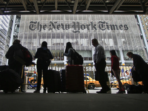 Pedestrians wait for cabs across the street from The New York Times in 2014.