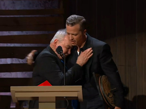 Album of the Year and Song of the Year award winner Jason Isbell hugs John Prine at the 2016 Americana Music Association Honors and Awards Ceremony.