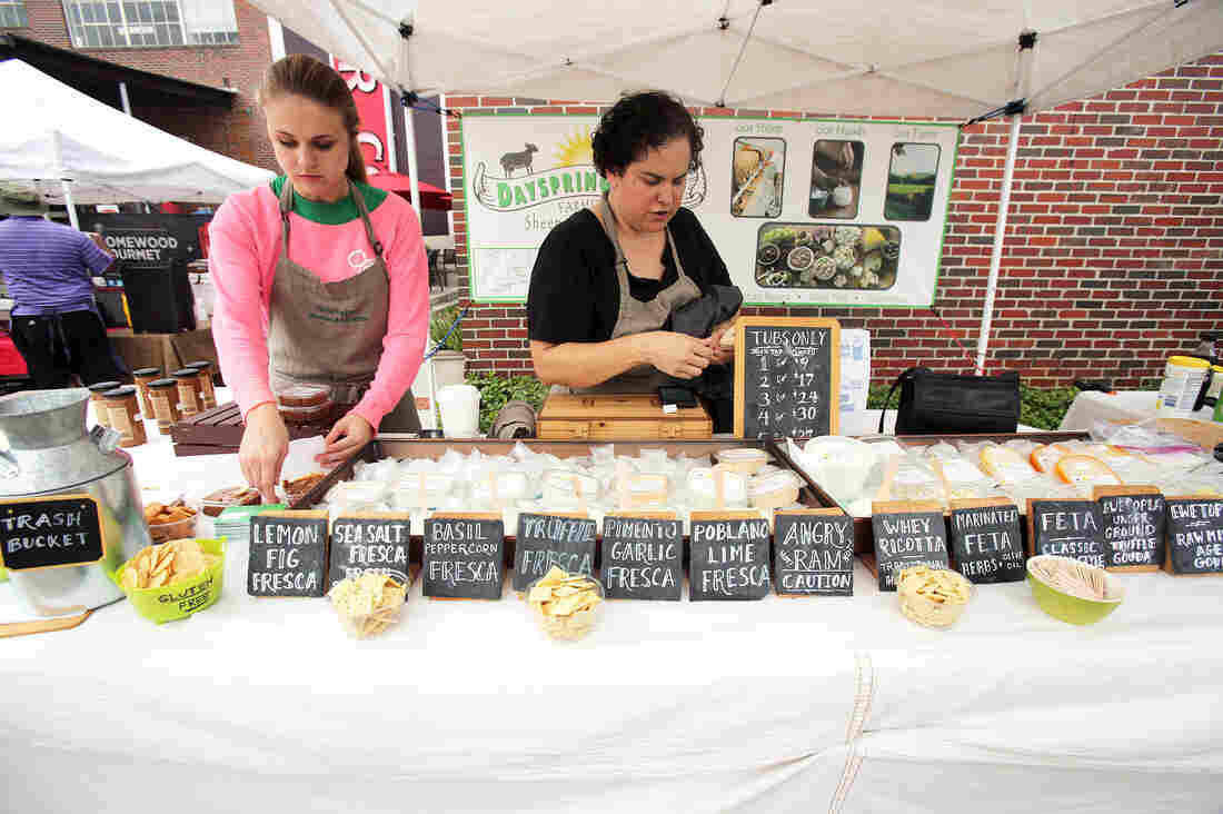 Ana Kelly, with Melody Weldon, a part-time employee, quickly gets the booth ready for business at Pepper Place Market, held on Saturdays in Birmingham, Ala. Names of the cheeses reflect the ingredients.